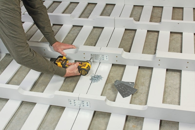 Builder fastening pallets together with mending plates - DIY platform bed