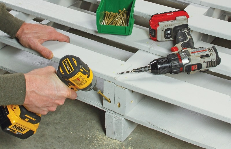 Builder driving wood screws into connected pallets - DIY platform bed